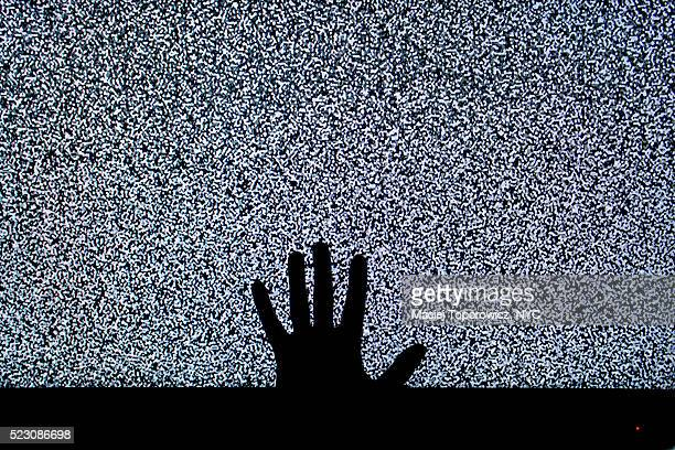 Silhouette of a hand against TV screen with static.