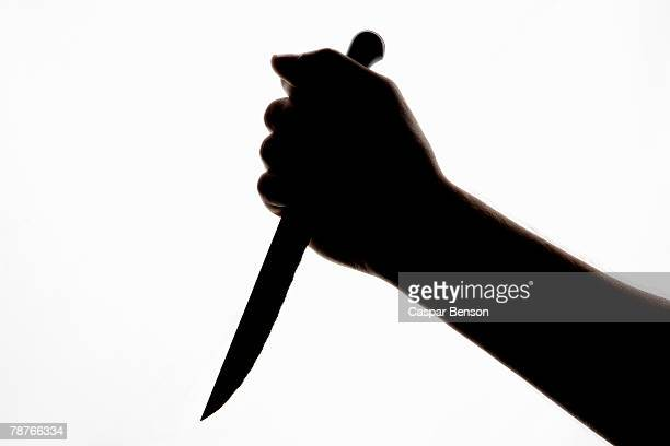 A silhouette of a hand holding a knife