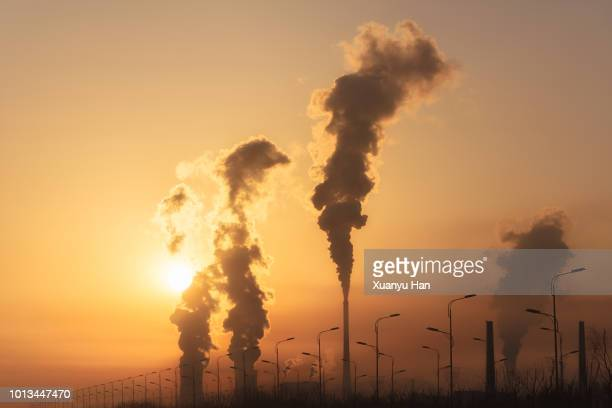 silhouette of a high industrial pipe with the sun behind it - climate stock pictures, royalty-free photos & images