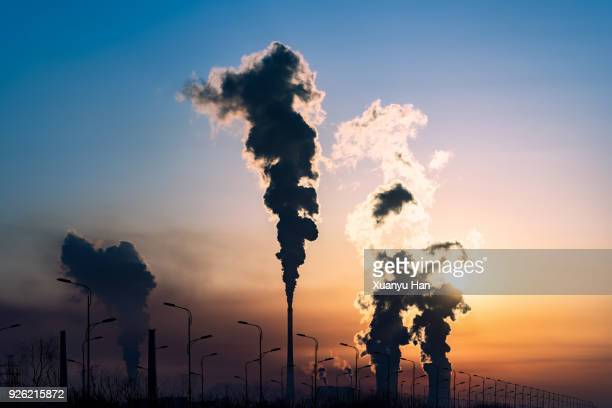 silhouette of a high industrial pipe with the sun behind it - carbon dioxide stock photos and pictures