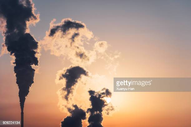 silhouette of a high industrial pipe with the sun behind it - carbon dioxide bildbanksfoton och bilder