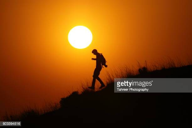 Silhouette of a hiker going downhill