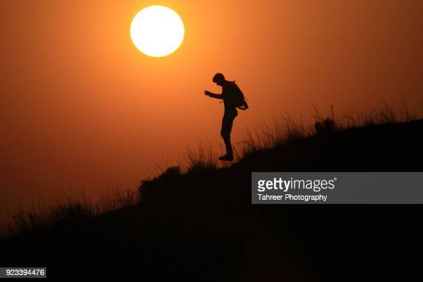 Silhouette of a hiker jumping downhill