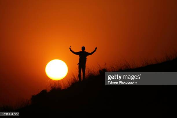 silhouette of a hiker standing on hill while sun is setting in the background - イスラマバード ストックフォトと画像