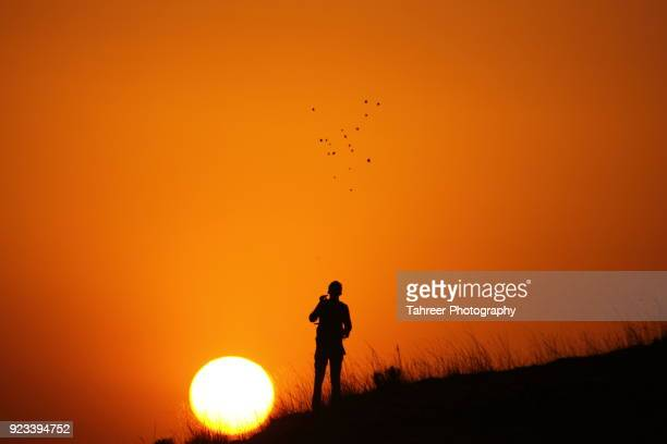 Silhouette of a hiker throwing pebbles towards sky