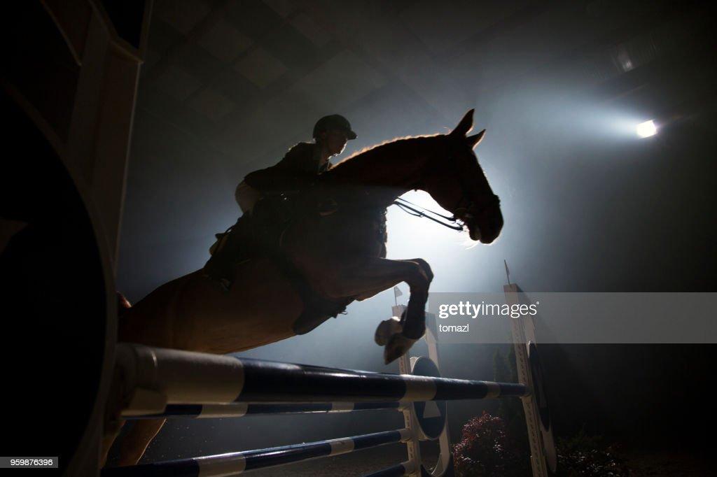 Silhouette eines Pferdes und ein Fahrer einen Sprung über die Hürde : Stock-Foto
