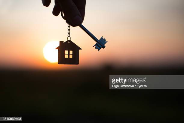 silhouette of a house figure with a key, a pen with a keychain on the background of the sunset. - mortgage stock pictures, royalty-free photos & images