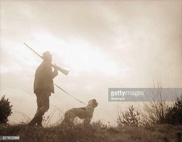 Silhouette of a hunter with his bird dog Photograph circa 1950's