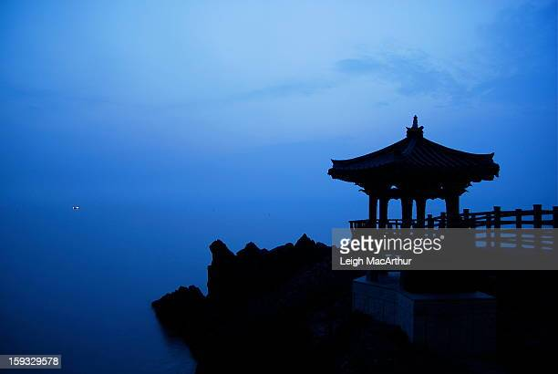 CONTENT] A silhouette of a Korean gazebo with a fishing boat with its lights are seen in the distance off the eastern coast of South Korea in a city...