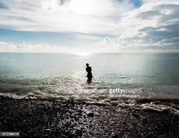 Silhouette of a Lone Man Standing in the Sea