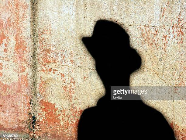 Silhouette of a man against a sandstone wall.