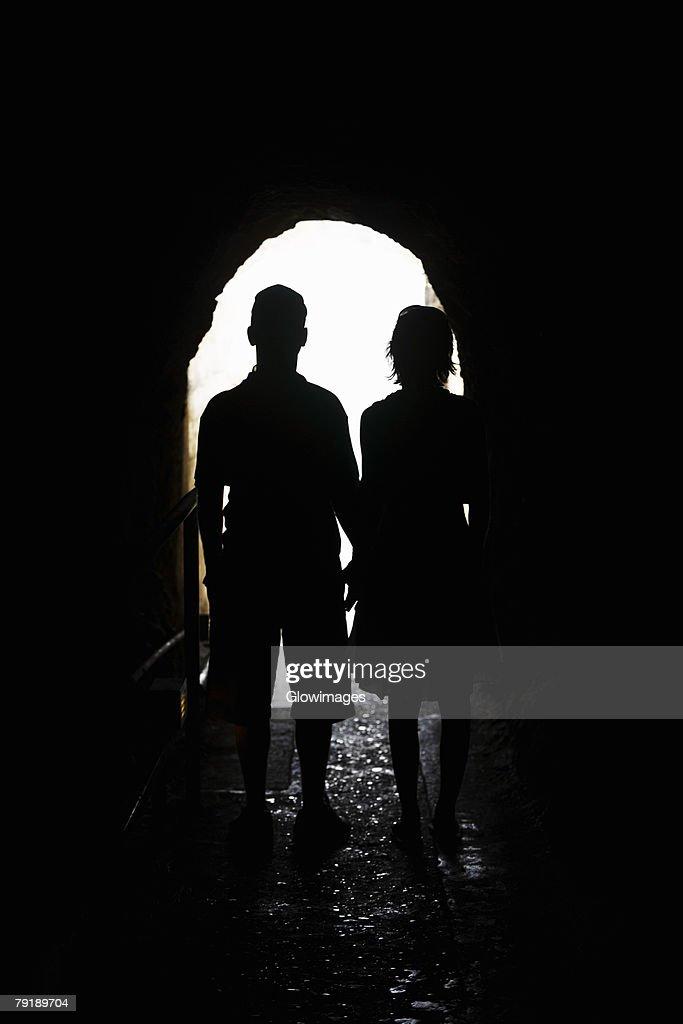 Silhouette of a man and a woman standing in an archway, Diamond Head, Waikiki Beach, Honolulu, Oahu, Hawaii Islands, USA : Stock Photo