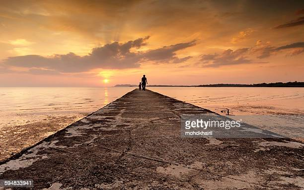 Silhouette of a man and his son standing at the end of a jetty, Port Dickson, Malaysia