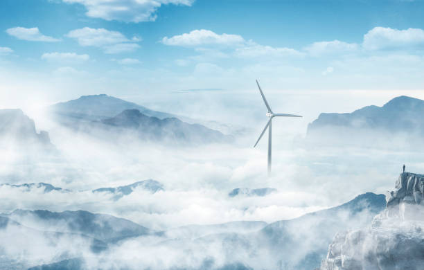 Silhouette of a man at the top of a cliff looking at a wind turbine in a sea of clouds