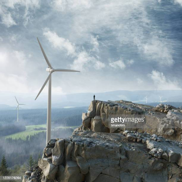 silhouette of a man at the top of a cliff looking at the horizon with wind turbines - umweltschutz stock-fotos und bilder