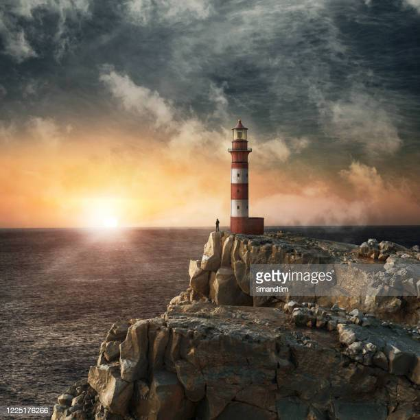 silhouette of a man at the top of a cliff looking at the sunrise beside a lighthouse - horizon stock pictures, royalty-free photos & images