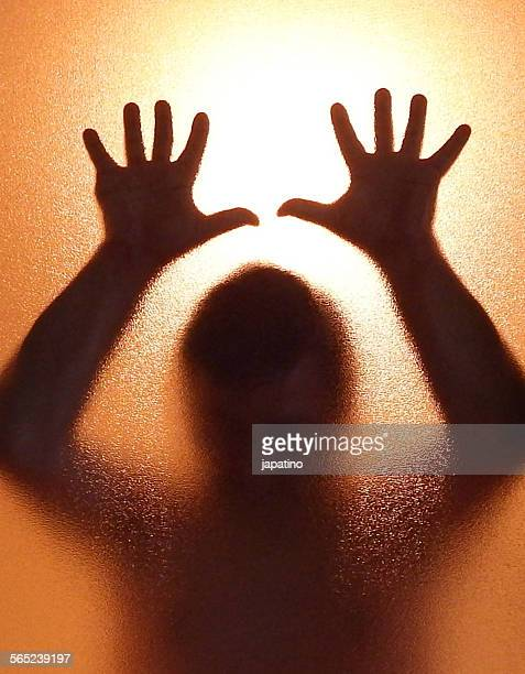 silhouette of a man behind a glass. despair