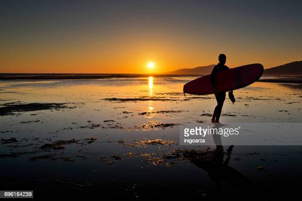 Silhouette of a man carrying a surfboard o beach, Los Lances, Tarifa, Cadiz, Andalucia, Spain