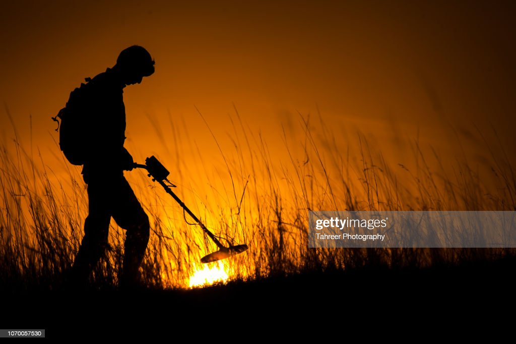 Silhouette of a man carrying an underground metal detector and looking for mines : Stock Photo