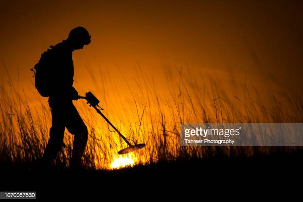Silhouette of a man carrying an underground metal detector and looking for mines