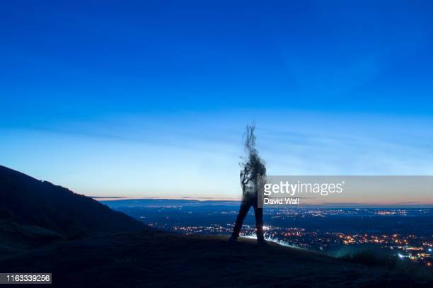 a silhouette of a man disappearing and turning into smoke. standing on a hill. looking out on city lights just before sunrise. - post traumatic stress disorder stock pictures, royalty-free photos & images