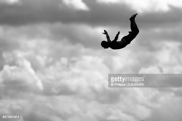 Silhouette of a man doing a swallow dive against clouds
