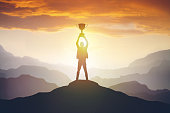 Silhouette of a man holding a trophy at sunset