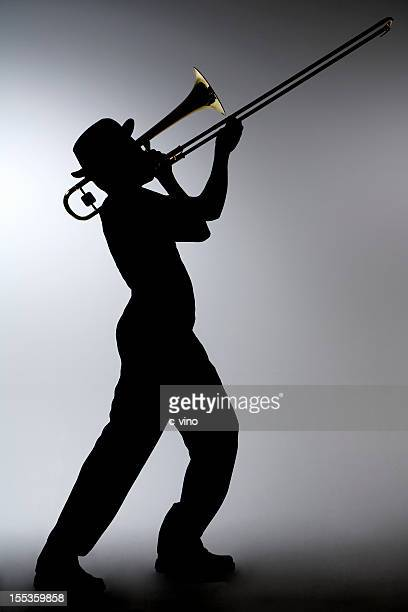 Silhouette of a man in a porkpie hat playing the trombone