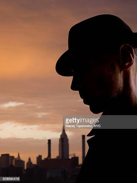 Silhouette of a man in hat against Manhattan skyline.