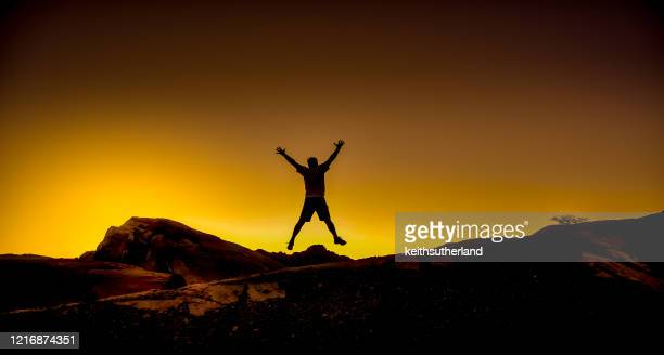 silhouette of a man jumping in the air in the desert, valley of fire state park, nevada, usa - legs apart stock pictures, royalty-free photos & images
