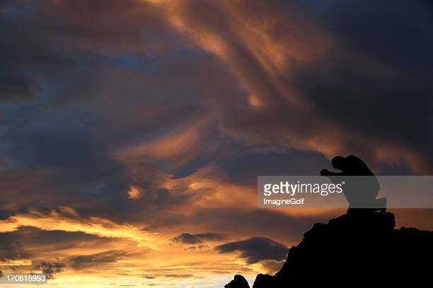 silhouette of a man kneeling and praying on mountain - forgiveness stock pictures, royalty-free photos & images