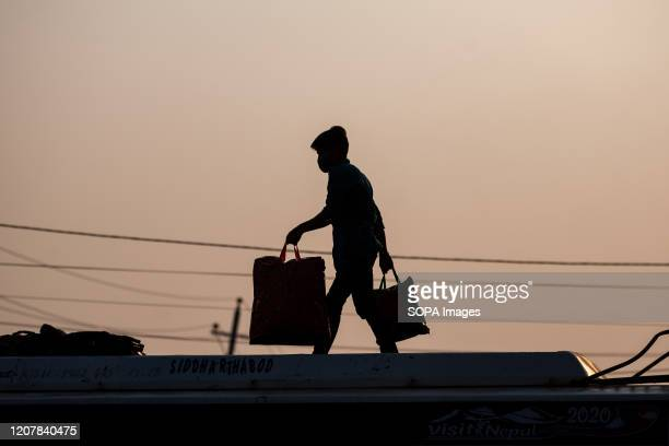Silhouette of a man loading luggage onto a long distance bus leaving Kathmandu amid Coronavirus threats. Nepalese government decided to close down...