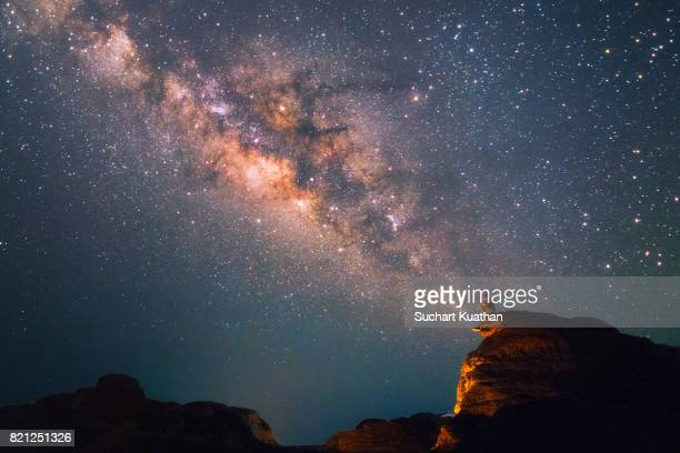 silhouette of a man looking at the milky way stars shining above the grand canyon of thailand (sam phan bok) - milky way stock pictures, royalty-free photos & images