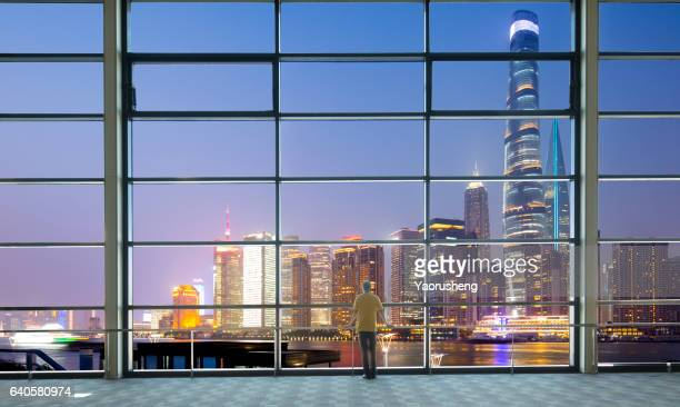 Silhouette of a Man looking out of window at night.background is Shanghai city night