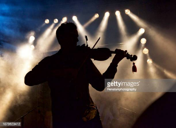 silhouette of a man on stage playing the violin - オーケストラ ストックフォトと画像
