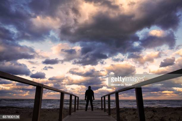 silhouette of a man on the pier leading to the sea - molise foto e immagini stock