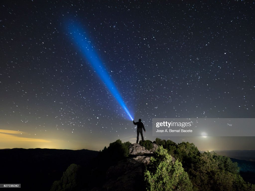 Silhouette of a man on the top of a mountain in the night, with a lantern in the hand doing a beam of light on a sky of stars : Foto de stock