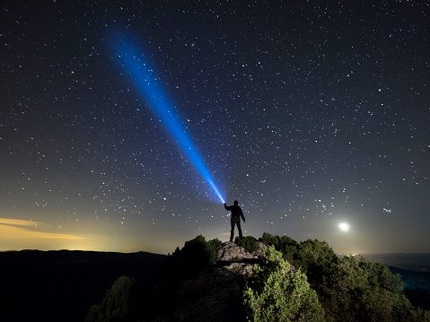 Silhouette of a man on the top of a mountain in the night, with a lantern in the hand doing a beam of light on a sky of stars - gettyimageskorea