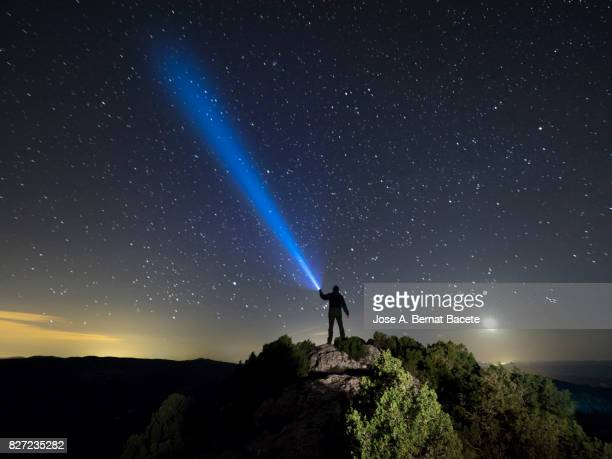 Silhouette of a man on the top of a mountain in the night, with a lantern in the hand doing a beam of light on a sky of stars