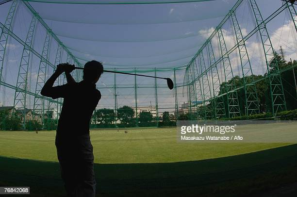 silhouette of a man playing a golf stroke at a golf range - ゴルフ練習場 ストックフォトと画像