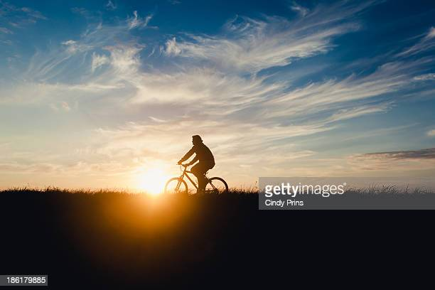 Silhouette of a man riding a bicycle at sunset