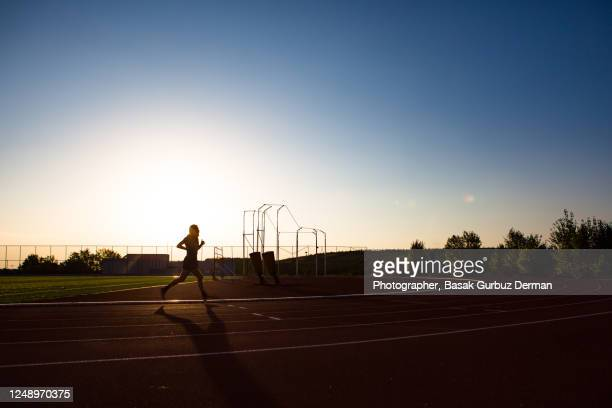 silhouette of a man running on a track - extra long stock pictures, royalty-free photos & images