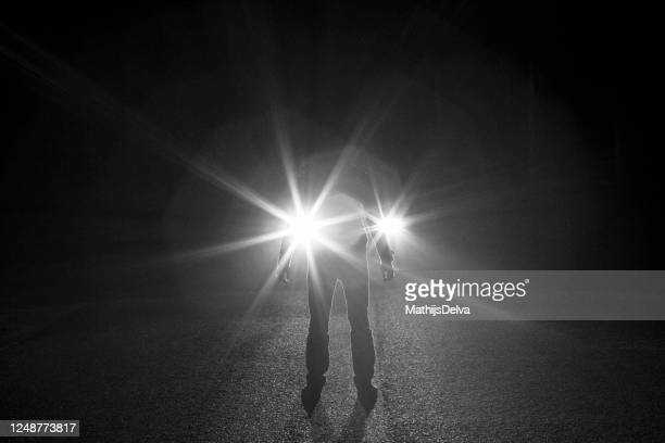 silhouette of a man standing in front of a car's headlights at night, belgium - fugitive stock pictures, royalty-free photos & images