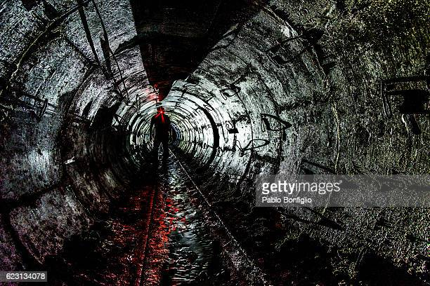 silhouette of a man standing in the underground drainage system in kiev, ukraine - ウクライナ トンネル ストックフォトと画像