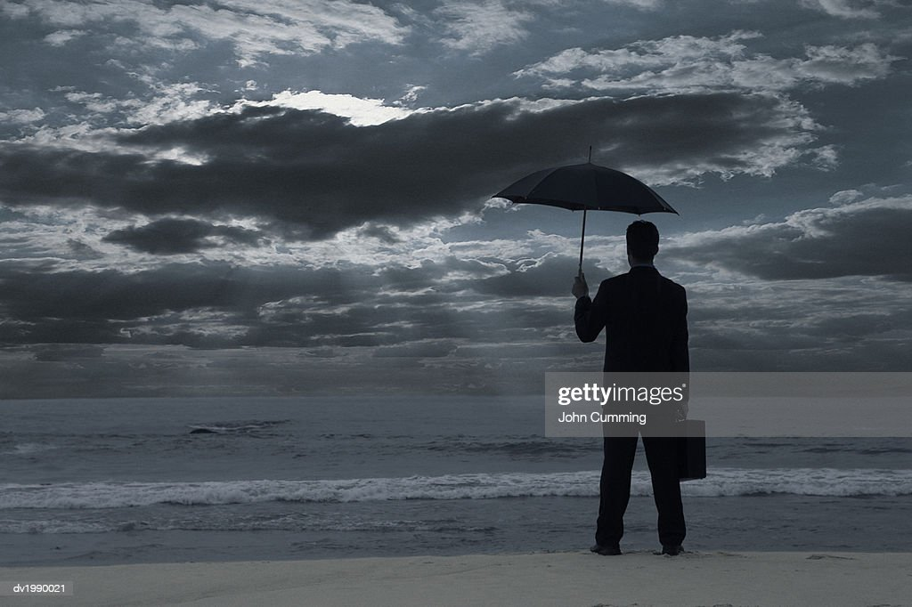 Silhouette of a Man Standing on a Moody Beach and Holding an Umbrella : Stock Photo