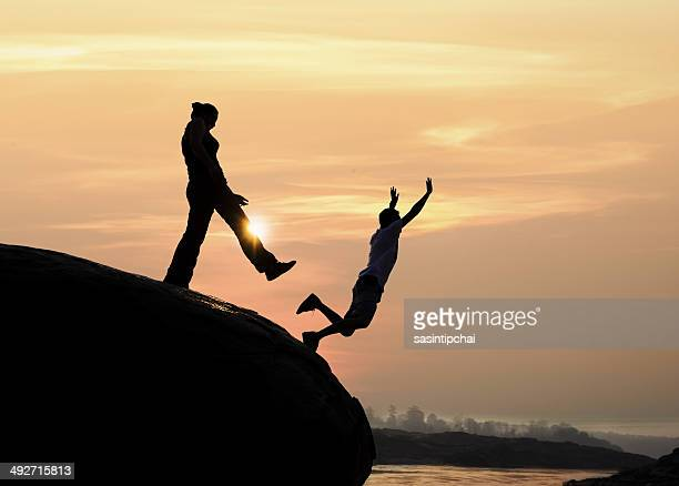 Silhouette of a man standing on rock kicking a woman