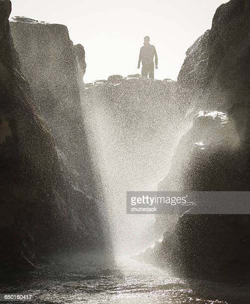 Silhouette of a man standing on rocks by ocean tide pool