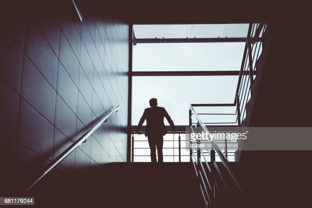 Silhouette of a man standing on steps at airport