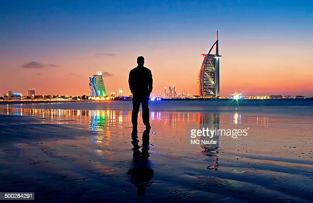 Silhouette of a man standing on the beach facing Burj Arab in Dubai just after the sunset.