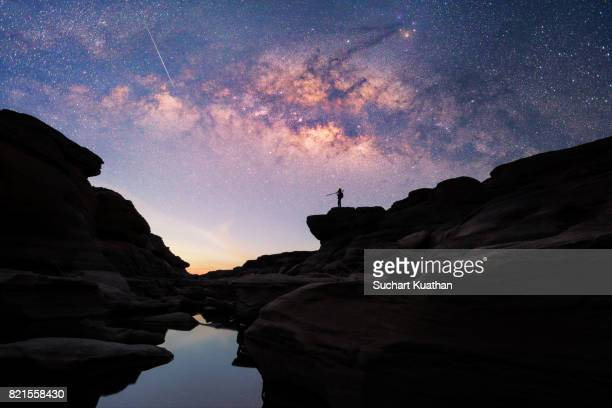 silhouette of a man standing on the rock looks at the milky way stars and the meteor at stone mountain. - meteor stock pictures, royalty-free photos & images